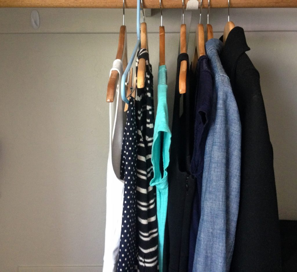 minimalist ethical capsule wardrobe hanging in closet, image